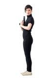 Σκληρός επικίνδυνος θηλυκός κατάσκοπος με το πιστόλι που ξανακοιτάζει πέρα από τον ώμο Στοκ φωτογραφία με δικαίωμα ελεύθερης χρήσης