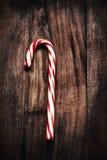 Σκληρός κάλαμος καραμελών μεντών Χριστουγέννων ριγωτός πέρα από το ξύλινο σκοτεινό backgrou Στοκ Εικόνες
