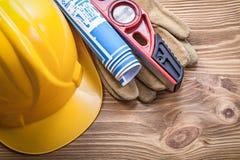 Σκληρό μπλε σχεδιάγραμμα επιπέδων κατασκευής γαντιών ασφάλειας καπέλων στο ξύλο Στοκ Εικόνες