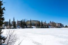 Σλοβακία: Θέρετρο pleso Strbske, άποψη της παγωμένης λίμνης το χειμώνα και θέρετρο ξενοδοχείων ανωτέρω μπλε ουρανός Στοκ Εικόνες