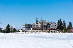 Σλοβακία: Θέρετρο pleso Strbske, άποψη της παγωμένης λίμνης το χειμώνα και θέρετρο ξενοδοχείων ανωτέρω μπλε ουρανός Στοκ Φωτογραφία