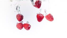 Σμέουρα που καταβρέχουν στο κρύσταλλο - καθαρίστε το νερό με τις αεροφυσαλίδες στοκ φωτογραφίες με δικαίωμα ελεύθερης χρήσης
