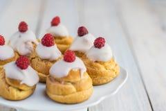 Σμέουρα Profiteroles με την άσπρη σοκολάτα στο άσπρο πιάτο Στοκ Φωτογραφίες
