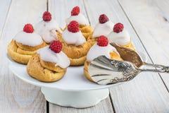 Σμέουρα Profiteroles με την άσπρη σοκολάτα στο άσπρο πνεύμα πιάτων Στοκ Εικόνες