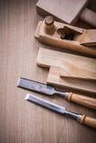 Σμίλες μετάλλων αεροπλάνων ξυρίσματος σφυρών χεριών και ξύλινο στήριγμα σε καφετή Στοκ εικόνα με δικαίωμα ελεύθερης χρήσης