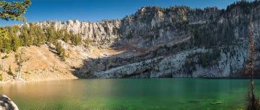 Σμαραγδένια πράσινη λίμνη με τους απότομους βράχους βουνών Στοκ εικόνες με δικαίωμα ελεύθερης χρήσης