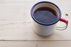 Σμαλτωμένη κούπα στρατοπέδευσης με το τσάι σειράς σε μια ξύλινη σύσταση Στοκ φωτογραφία με δικαίωμα ελεύθερης χρήσης