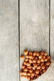 Σμιλευμένα φουντούκια σε μια τσάντα burlap σε έναν γκρίζο ξύλινο πίνακα Φρέσκος που συγκομίζεται οργανικός στοκ εικόνες