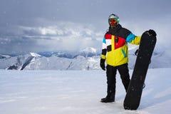 Σνόουμπορντ εκμετάλλευσης Snowboarder στα χέρια των χιονοπτώσεων Στοκ Εικόνες