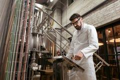 Σοβαρά πιέζοντας κουμπιά ατόμων στο εργοστάσιο μπύρας Στοκ φωτογραφία με δικαίωμα ελεύθερης χρήσης