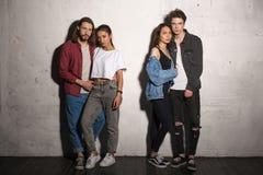 Σοβαρά hipsters που αγαπούν τα ζεύγη που στέκονται πέρα από το γκρίζο υπόβαθρο Στοκ Εικόνα