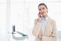 Σοβαρή έξυπνη καφετιά μαλλιαρή επιχειρηματίας που κάνει ένα τηλεφώνημα Στοκ εικόνες με δικαίωμα ελεύθερης χρήσης