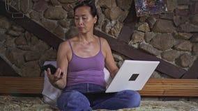 Σοβαρή ασιατική δακτυλογράφηση γυναικών στο lap-top στο σπίτι και έλεγχος του τηλεφώνου απόθεμα βίντεο
