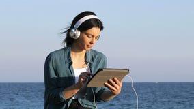 Σοβαρή γυναίκα που κοιτάζει βιαστικά και περιεκτικότητα σε ταμπλέτες ακούσματος φιλμ μικρού μήκους
