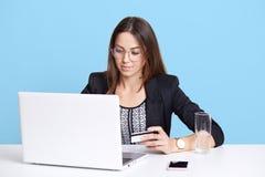 Σοβαρή επιτυχής νέα θηλυκή συνεδρίαση που απομονώνεται πέρα από το ανοικτό μπλε υπόβαθρο, πιστωτική κάρτα εκμετάλλευσης στο χέρι  στοκ φωτογραφία με δικαίωμα ελεύθερης χρήσης
