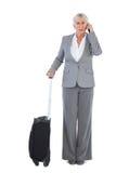 Σοβαρή επιχειρηματίας με τις αποσκευές της και την κλήση κάποιου Στοκ φωτογραφία με δικαίωμα ελεύθερης χρήσης