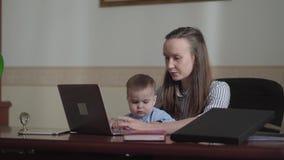Σοβαρή επιχειρηματίας πορτρέτου με το μωρό και φορητός προσωπικός υπολογιστής που λειτουργεί στο γραφείο φιλμ μικρού μήκους