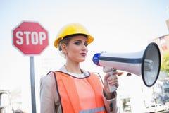 Σοβαρή επιχειρηματίας που φορά τα ενδύματα οικοδόμων που κρατούν megaphone Στοκ εικόνες με δικαίωμα ελεύθερης χρήσης