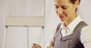 Σοβαρή επιχειρηματίας που χρησιμοποιεί το lap-top της και το smartphone της φιλμ μικρού μήκους
