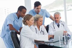 Σοβαρή ιατρική ομάδα που χρησιμοποιεί ένα lap-top Στοκ φωτογραφία με δικαίωμα ελεύθερης χρήσης