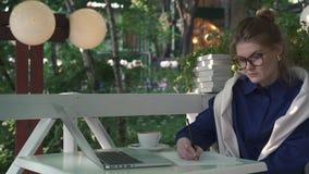 Σοβαρή καυκάσια επιχειρηματίας που γράφει σε έναν θερινό καφέ Επιχειρησιακή στρατηγική απόθεμα βίντεο