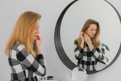 Σοβαρή κομψή γυναίκα κοντά στον καθρέφτη στοκ φωτογραφία