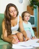 Σοβαρή μητέρα που υπογράφει το έγγραφο Στοκ Εικόνες