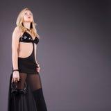 Σοβαρή νέα γυναίκα μόδας με τα ακουστικά Στοκ Εικόνα