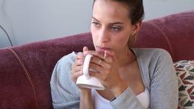 Σοβαρή νέα γυναίκα που κοιτάζει μέσω του παραθύρου πίνοντας τον καφέ στον καναπέ στο σπίτι