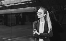 Σοβαρή νέα γυναίκα στο κοστούμι και τα γυαλιά, γραπτά Στοκ Εικόνα