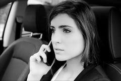 Σοβαρή νέα επιχειρησιακή γυναίκα στο τηλέφωνο στο γραπτό πορτρέτο αυτοκινήτων στοκ εικόνα με δικαίωμα ελεύθερης χρήσης