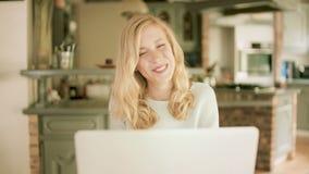 Σοβαρή ξανθή δακτυλογράφηση γυναικών στο lap-top της απόθεμα βίντεο