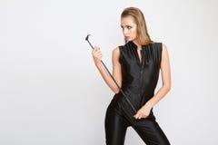 Σοβαρή όμορφη γυναίκα μόδας στο μαύρο γενικό μαστίγιο εκμετάλλευσης Στοκ Εικόνα