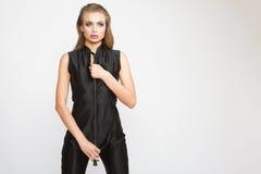Σοβαρή όμορφη γυναίκα μόδας στο μαύρο γενικό μαστίγιο εκμετάλλευσης Στοκ Φωτογραφία