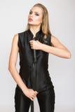 Σοβαρή όμορφη γυναίκα μόδας στο μαύρο γενικό μαστίγιο εκμετάλλευσης Στοκ φωτογραφία με δικαίωμα ελεύθερης χρήσης