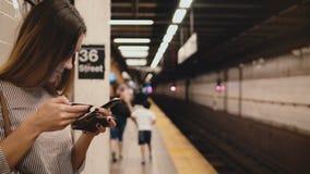 Σοβαρή όμορφη τονισμένη γυναίκα στο smartphone εκμετάλλευσης πλατφορμών υ φιλμ μικρού μήκους