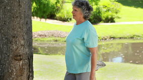 Σοβαρή ώριμη γυναίκα που κάνει τις ασκήσεις ικανότητας φιλμ μικρού μήκους