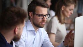 Σοβαροί άνδρες υπάλληλοι που απασχολούνται μαζί να συζητήσει το πρόγραμμα υπολογιστών στην αρχή φιλμ μικρού μήκους