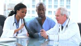 Σοβαροί γιατροί και ένας οικότροφος που εξετάζει μια ακτίνα X φιλμ μικρού μήκους