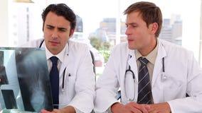Σοβαροί γιατροί που εξετάζουν μαζί μια ακτίνα X απόθεμα βίντεο