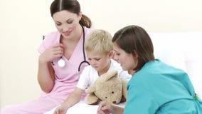 Σοβαροί γιατροί που εξετάζουν τη θωρακική ακτίνα X ενός παιδιού απόθεμα βίντεο