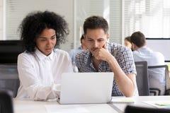 Σοβαροί διαφορετικοί συνάδελφοι γραφείων που συζητούν το σε απευθείας σύνδεση resu προγράμματος στοκ φωτογραφίες