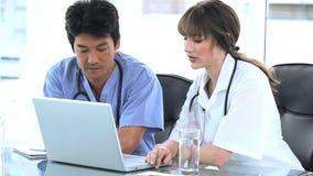 Σοβαροί επαγγελματίες που μιλούν μαζί μπροστά από ένα lap-top απόθεμα βίντεο