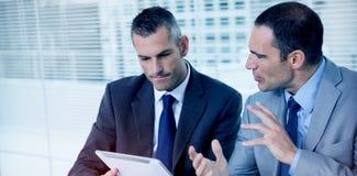 Σοβαροί επιχειρηματίες που αναλύουν τα έγγραφα σχετικά με την ταμπλέτα τους απεικόνιση αποθεμάτων
