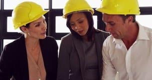Σοβαροί επιχειρηματίες που εργάζονται μαζί φορώντας το κράνος απόθεμα βίντεο