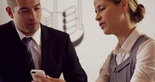 Σοβαροί επιχειρηματίες που εργάζονται μαζί smartphone απόθεμα βίντεο
