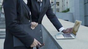Σοβαροί επιχειρηματίες που συζητούν την παρουσίαση για το lap-top κοντά στο κτίριο γραφείων απόθεμα βίντεο