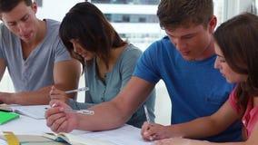 Σοβαροί σπουδαστές που βοηθούν ο ένας τον άλλον εργαζόμενοι απόθεμα βίντεο