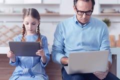 Σοβαροί συμπαθητικοί πατέρας και κόρη που χρησιμοποιούν τις τεχνολογικές συσκευές Στοκ Φωτογραφίες