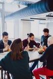 Σοβαροί συνάδελφοι που τρώνε στον πίνακα στο γραφείο στοκ φωτογραφία με δικαίωμα ελεύθερης χρήσης